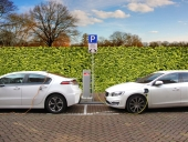 two hybrid electric cars are recharging